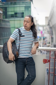Asain / thai-青い線のtシャツを着た中国人の長い黒髪の男が、スカイトレインの近くの肩にバックパックを持って考えています。
