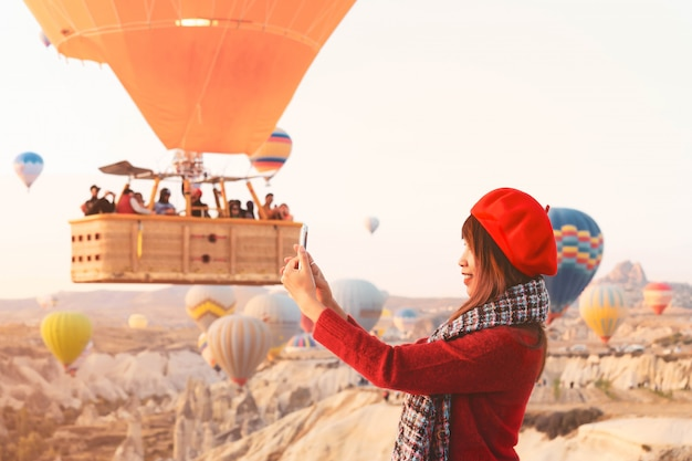 Asain woman enjoy taking pictures of hot air balloons flying over amazing rock landscape in cappadocia.