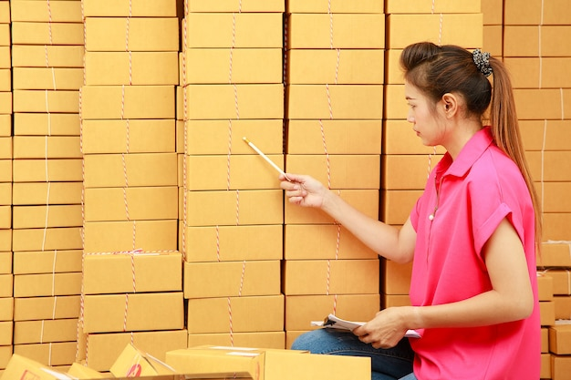 Asain 여성은 높은 소포 더미 앞에서 집에서 쇼핑 온라인 비즈니스에서 소포 상자를 세는 연필을 사용합니다