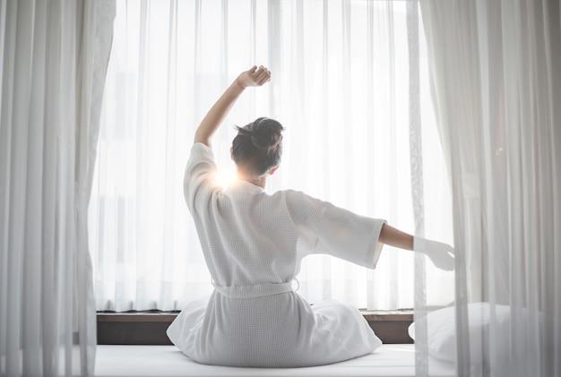 Asain женщина просыпается в своей постели.