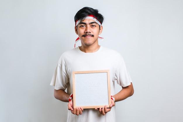 白地に隔離されたカメラに指で指している空白のボードを保持している赤と白のヘッドバンドを身に着けているアサン男