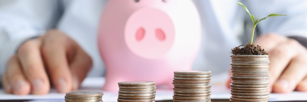 Ascending coin towers stand on table against background of pink piggy bank