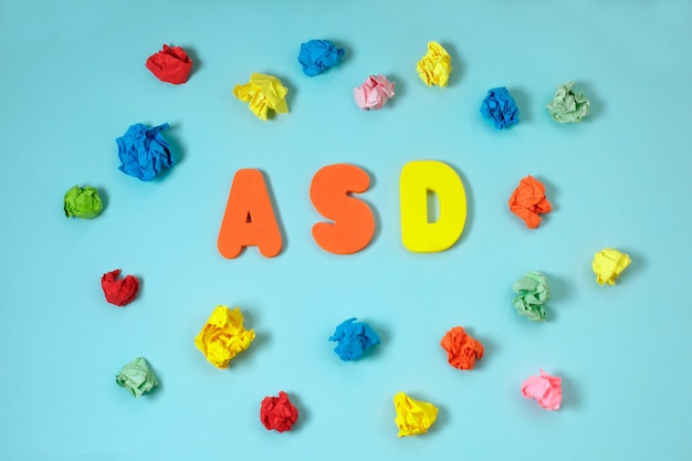Asd, autism concept with color letters and crumpled paper on blue background