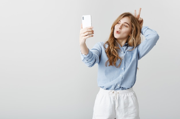 Not ashamed to be funny in front of camera. good-looking positive feminine girl with blond hair in blue blouse, taking selfie while making faces and showing v sign behind head, aping over gray wall