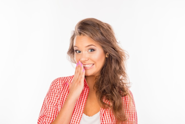 Ashamed young woman hiding mouth with her hand