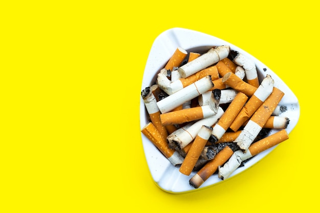 Ashtray and cigarettes on yellow background. copy space