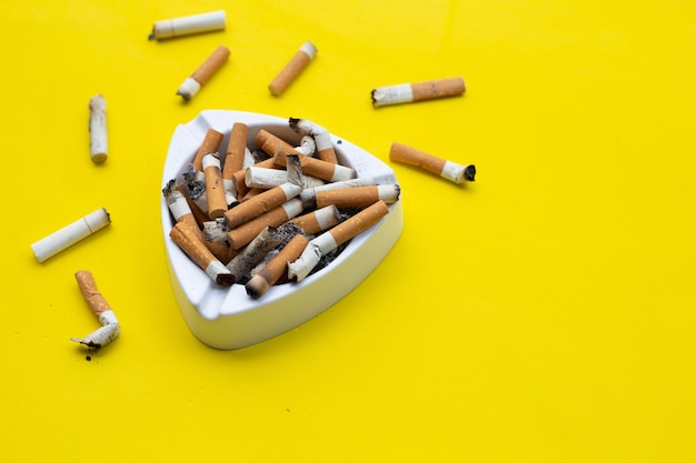 Ashtray and cigarettes on yellow surface
