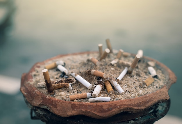 たばこの吸い殻がいっぱいの灰皿。灰皿でたばこを使用。