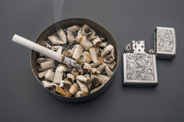 Ashtray smoking cigarette lighter on a gray table background
