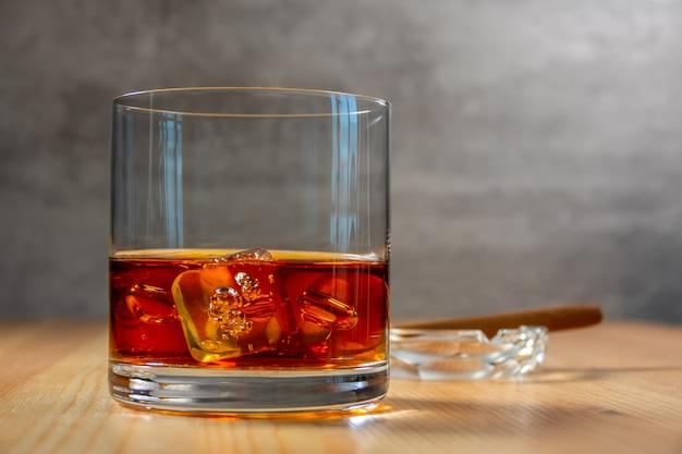 焦点ぼけの背景に葉巻を置いた灰皿。木製のテーブルに角氷とウイスキーのガラス