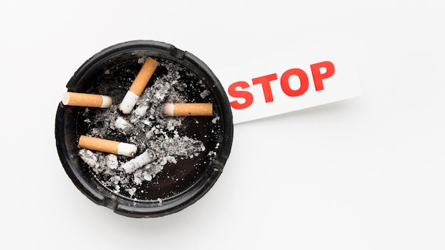 Ashtray with smoked cigarettes and stop habit message
