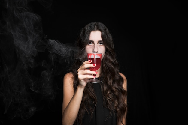 Ashy woman closing face by goblet with smoking red liquid