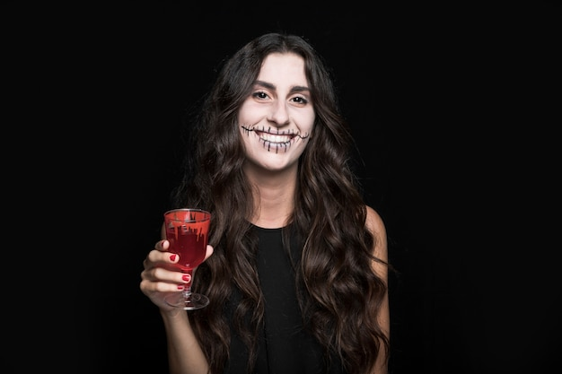 Ashy woman holding glass with red liquid