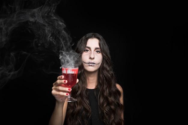 赤い燃焼液体とガラスを保持するashyの女性