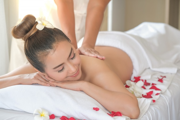 Asia beautiful woman during massage with essential oil in room spa thailand