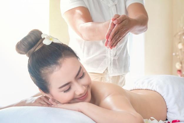 Asia beautiful  woman enjoying a salt scrub massage at the health spa in thailand