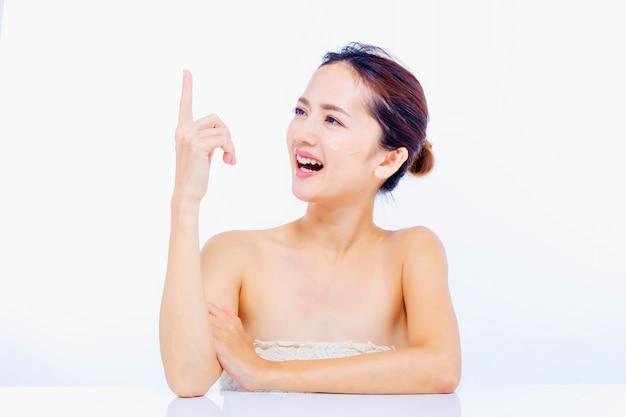 깨끗하고 신선한 피부 터치 자신의 얼굴과 그물 라스와 하얀 드레스를 입고 아시아 아름 다운 젊은 여자