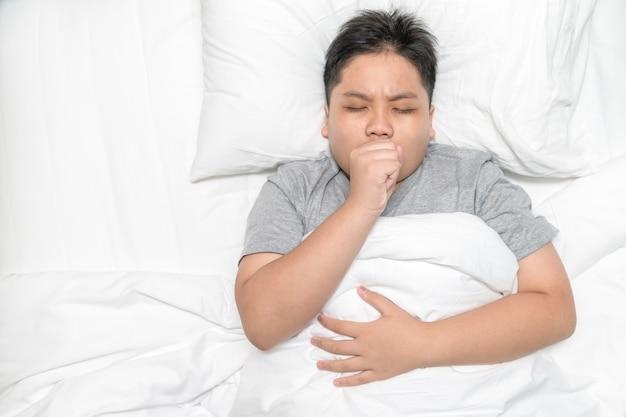 アジアの少年は咳をしてベッドに横たわっています、ヘルスケアとcovid-19コンセプト