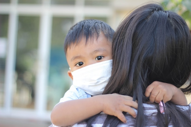 Азиатский мальчик в маске для лица для защиты от вируса короны и загрязнения воздуха pm2,5 с размытым фоном.