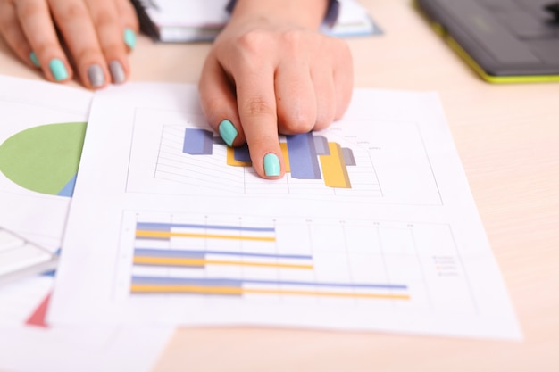 Asia business woman analyzing investment charts on desk
