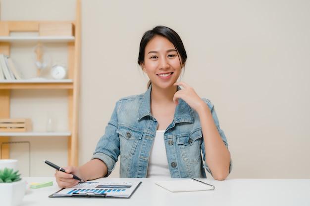 アジアビジネスの女性が幸せな笑みを浮かべて、自宅のオフィスでリラックスしながらカメラを探しています。