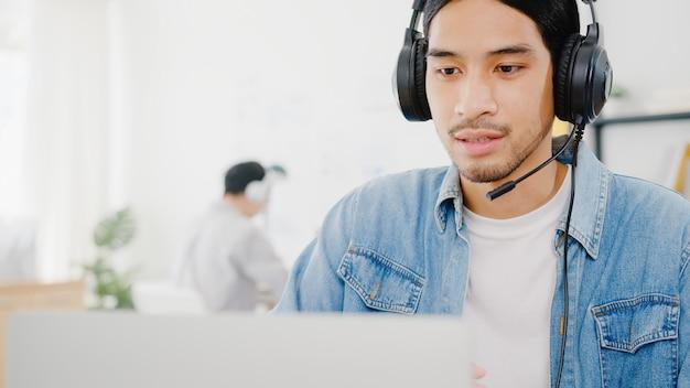 Азиатский бизнесмен социальное дистанцирование в новой нормальной ситуации для предотвращения вирусов с помощью презентации ноутбука коллеге о плане в видеозвонке во время работы в домашнем офисе. образ жизни после вируса короны.