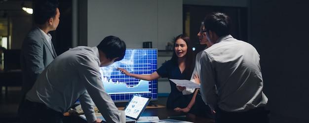 アジアのビジネスマンとビジネスウーマンがブレーンストーミングのアイデアを会議して、ビジネスプレゼンテーションプロジェクトの同僚が一緒に作業して成功戦略を計画し、小さなモダンな夜のオフィスでチームワークを楽しみます。