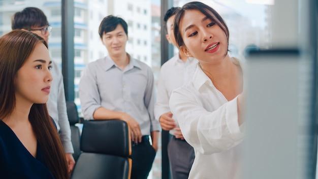 アジアのビジネスマンとビジネスウーマンがブレーンストーミングのアイデアを満たし、ビジネスプレゼンテーションプロジェクトの同僚が共同で作業を計画して成功戦略を計画し、小さな近代的なオフィスでチームワークを楽しみます。