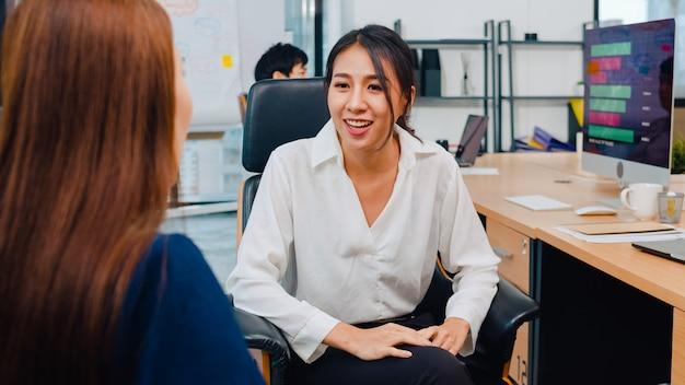 アジアのビジネスマンがオフィスでプロジェクトの作業計画の成功戦略についてアイデアをブレインストーミングしている会話やコミュニケーション会議を持つ就職の面接の同僚について話し合っているインターンとチャット。