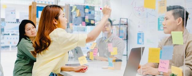 비즈니스 브레인 스토밍 회의를 함께 논의하는 아시아 기업인들이 데이터를 공유하고 아크릴 파티션에 글을 쓰면 새로운 일반 사무실로 돌아옵니다. 라이프 스타일 사회적 거리두기 및 코로나 바이러스 이후 작업.