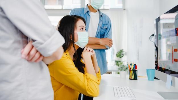 新しいプロジェクトの同僚に関するアイデアをブレインストーミングし、新しい通常のオフィスで保護マスクを着用するコンピュータープレゼンテーション会議を使用しているアジアのビジネスマン。ライフスタイルとコロナウイルス後の仕事。
