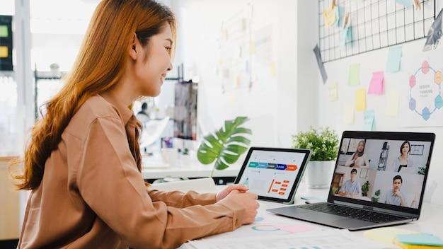 Азиатские бизнесмены, использующие ноутбук, разговаривают с коллегами, обсуждая бизнес-мозговой штурм о плане во время видеовстречи в новом обычном офисе.