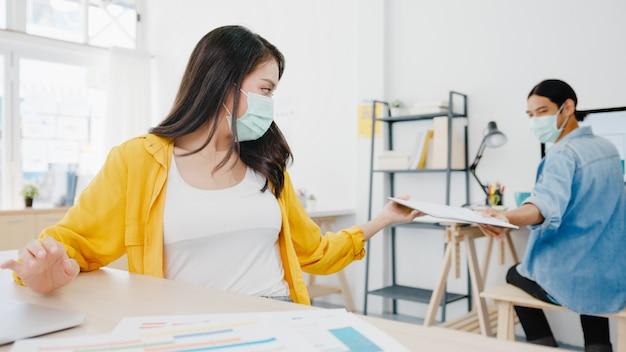 アジアのビジネスマンは、ウイルスの予防とオフィスでの距離を保ちながら文書を渡すための新しい通常の状況での社会的距離を保つためにフェイスマスクを着用します。コロナウイルス後のライフスタイルと仕事。