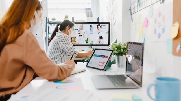 아시아 기업인들은 새로운 일반 사무실에서 화상 통화 회의 계획에 대한 브레인 스토밍을 논의하는 동료들과 데스크톱 대화를 사용하여 안면 마스크를 착용합니다.