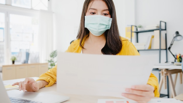 Asia businesswoman entrepreneur wearing medical face mask for social distancing in new normal situation for virus prevention while using laptop back at work in office. lifestyle after corona virus.