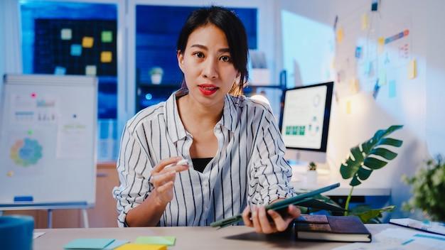 사무실 밤에 일하는 동안 화상 통화 계획에 대해 동료에게 카메라 프리젠 테이션을보고 바이러스 예방을위한 새로운 노멀에서 아시아 사업가 사회적 거리.