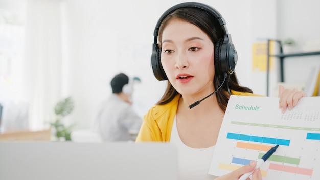 職場でのビデオ通話の計画について同僚にノートパソコンのプレゼンテーションを使用しながら、ウイルス防止のための新しい通常の状況でアジアの実業家の社会的距離。コロナウイルス後の生活。