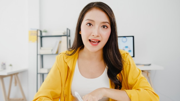 Asia businesswoman social distancing in new normal situation for virus prevention looking at camera presentation to friends about plan in video call while work in office. lifestyle after corona virus.