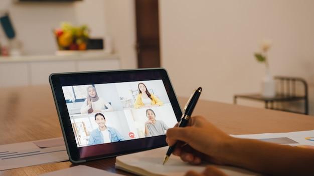 デジタルタブレットを使用しているアジアの実業家は、自宅のキッチンでリモートで作業しながら、ビデオ通話のブレインストーミングオンライン会議で計画について同僚と話します。