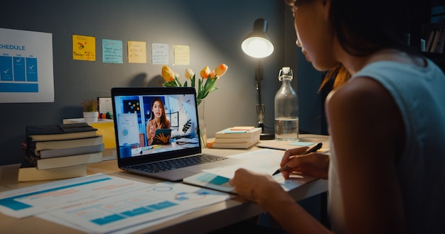 Asia businesswoman using laptop talk to colleagues about plan in video call meeting at living room at home. working from house overload at night, remotely, social distance, quarantine for coronavirus.