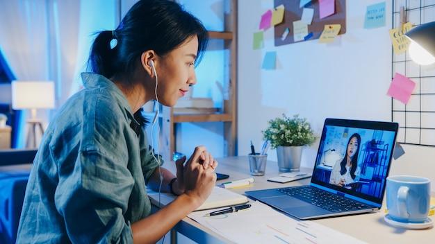La donna d'affari asiatica che utilizza il laptop parla con i colleghi del piano in una riunione di videochiamata in soggiorno.
