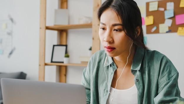 La donna d'affari asiatica che utilizza il laptop parla con i colleghi del piano in videochiamata mentre lavora in modo intelligente da casa in soggiorno