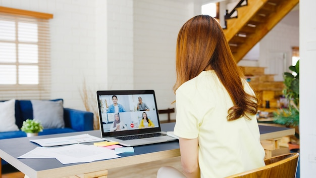 ラップトップを使用してアジアの実業家が自宅のリビングルームで作業中に同僚とビデオ通話会議の計画について話します。自己隔離、社会的距離、コロナウイルス防止のための検疫。