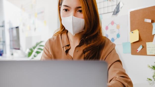 아시아 사업가는 사무실에서 일하는 동안 화상 통화 계획에 대해 동료에게 노트북 프레젠테이션을 사용하는 동안 바이러스 예방을 위해 새로운 정상적인 상황에서 사회적 거리를두기 위해 얼굴 마스크를 착용합니다.