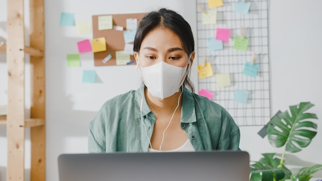 Азиатская деловая женщина в медицинской маске с ноутбуком разговаривает с коллегами о плане в видеозвонке, работая дома в гостиной.