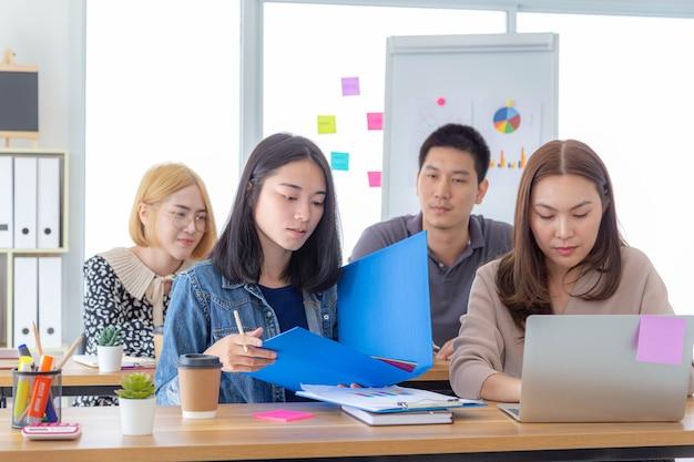 彼女の同僚がオフィスのテーブルで働く間、青い大きなオープンバインダーを保持しているアジアのビジネスウーマン