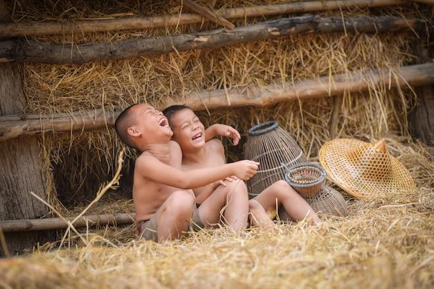 アジアの子供が笑うボーイフレンドハッピー面白い笑いと田舎で笑顔