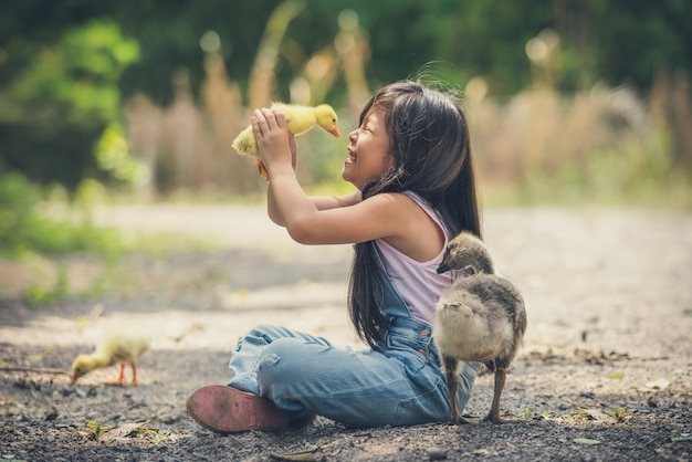 Asia children girl holds a duck in hands