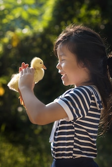 Asia children girl holds a duck in hands.