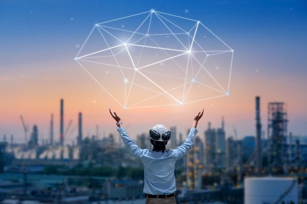 Стенд азиатского инженера, держащий рукой касание линии передачи данных на фоне нефтегазоперерабатывающего завода